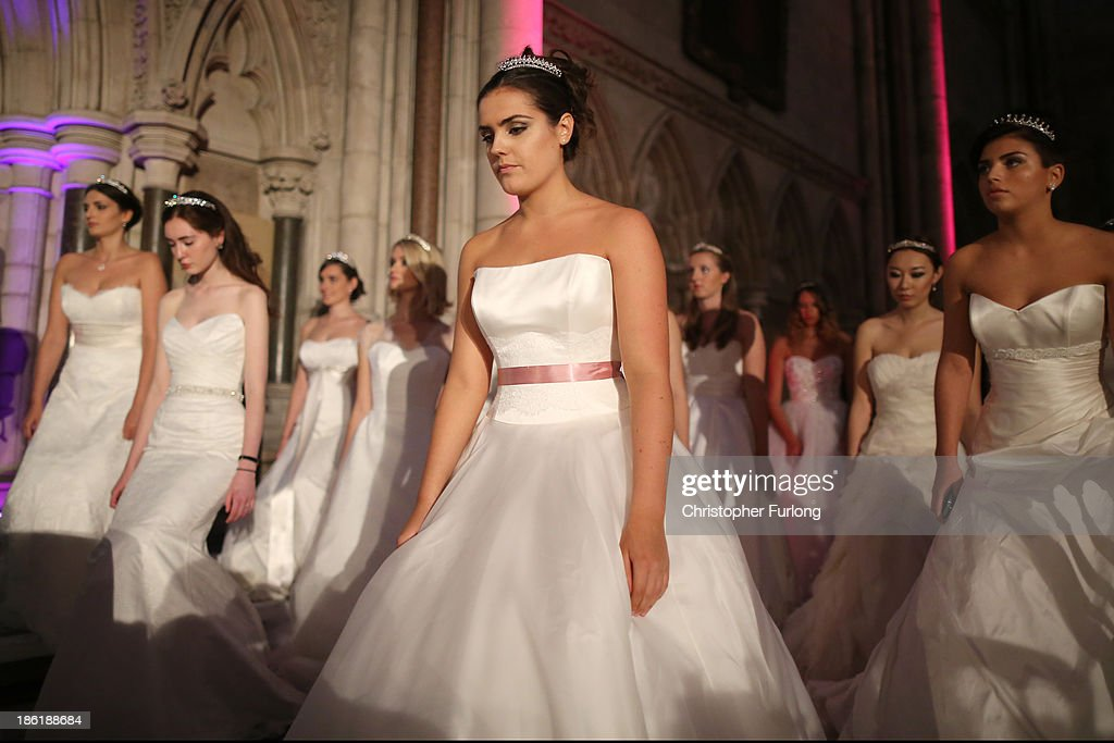 Debutantes rehearse their curtsey during the Queen Charlotte's Ball at the Royal Courts of Justice on October 26, 2013 in London, England. Queen Charlotte's Ball is the pinnacle event in the London Season. The London Season is rich in history and was formed over two hundred years ago when the custom of returning to London at the end of the hunting season was celebrated with glittering balls and high society events. The modern group of meticulously selected debutantes continue the tradition and celebrate their year of charity fund raising, etiquette classes and debut at The Queen Charlotte's Ball. The young ladies, usually aged between 17 and 20 and wearing designer dresses, attend the grand ball where they are presented to guests and curtsey to the Queen Charlotte Cake. King George III introduced the Queen Charlotte's Ball in 1780 to celebrate his wife's birthday and debutantes were traditionally presented to the King or Queen until 1958.