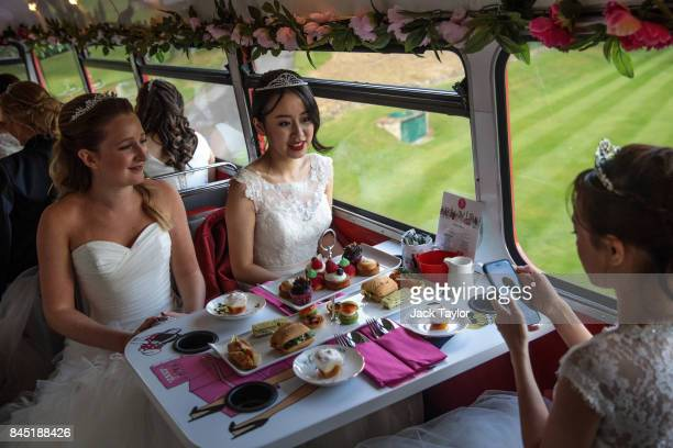 Debutantes sit at tables laid with cakes and sandwiches on the top deck of a Routemaster bus before leaving Boughton Monchelsea Place for the Queen...
