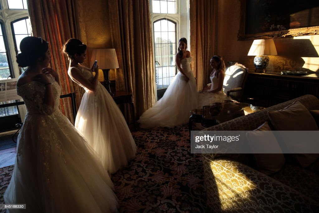 Debutantes take pictures at Leeds Castle during the Queen Charlotte's Ball on September 9, 2017 in Maidstone, England. In 1780 the first debutante's Ball was held by King George III to celebrate the birthday of his wife Queen Charlotte and raised money for a maternity hospital. Society girls were presented to the monarch and it became an annual event and important as a marriage market for the upper echelons of society. The London Season runs for six months of the year including sporting events, cocktail parties, dances and concerts and the Ball is the pinnacle of this season. After the present Queen terminated the practice of introducing debutantes at royal garden parties in 1957, Lady Howard de Walden followed by then editor of Tatler, Peter Townend, continued the tradition and on his death Peter nominated former debutantes Jennie Hallam-Peel and Patricia Woodall to take over running of The London Season. It is now focussed on raising money for children in need worldwide and the Queen Charlotte's Ball has been held in Shanghai and Dubai as well as various grand venues in London. This year the debutantes' gowns have been supplied by Berketex Brides and the cake, to which the debutantes curtsey, is made by Pretty Gorgeous Cakes.