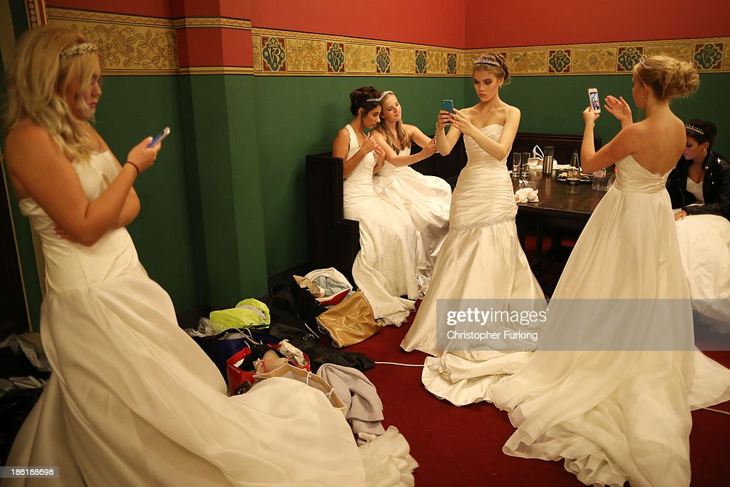 Debutantes use their smart phones to photograph themselves as they await the arrival of guests during the Queen Charlotte's Ball at the Royal Courts of Justice on October 26, 2013 in London, England. Queen Charlotte's Ball is the pinnacle event in the London Season. The London Season is rich in history and was formed over two hundred years ago when the custom of returning to London at the end of the hunting season was celebrated with glittering balls and high society events. The modern group of meticulously selected debutantes continue the tradition and celebrate their year of charity fund raising, etiquette classes and debut at The Queen Charlotte's Ball. The young ladies, usually aged between 17 and 20 and wearing designer dresses, attend the grand ball where they are presented to guests and curtsey to the Queen Charlotte Cake. King George III introduced the Queen Charlotte's Ball in 1780 to celebrate his wife's birthday and debutantes were traditionally presented to the King or Queen until 1958.