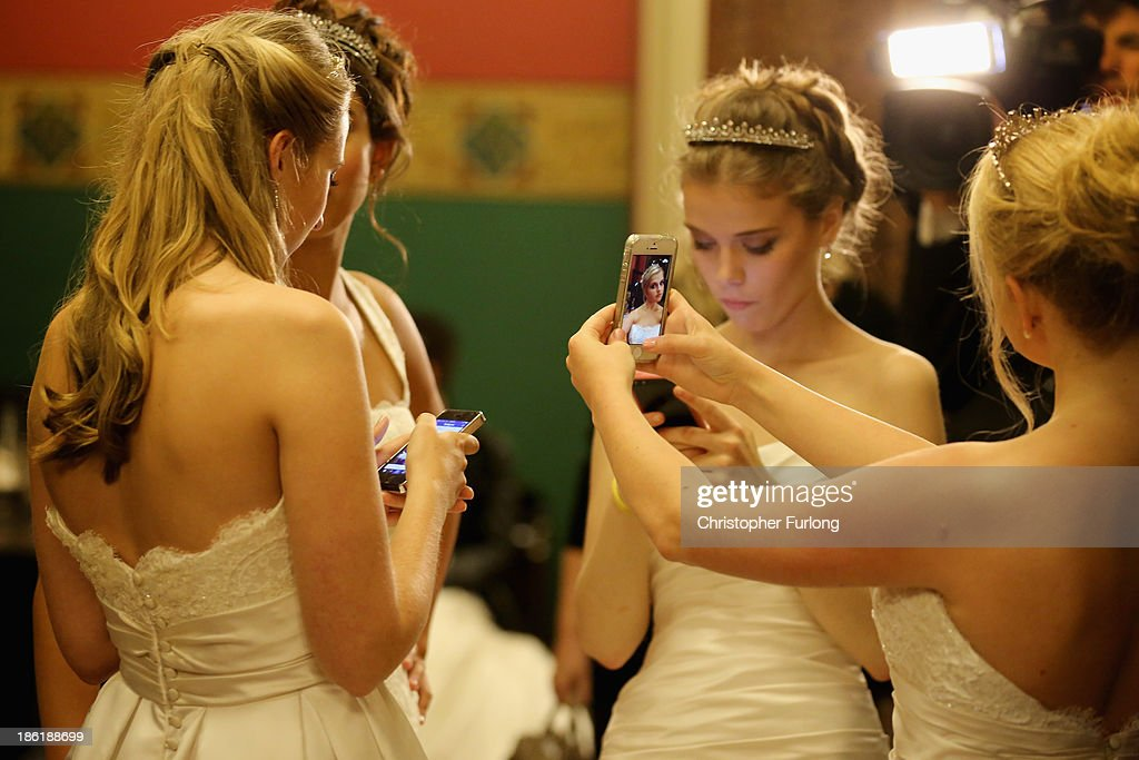 Debutantes use their smart phones to photograph themselves as they await the arrival of guests during the Queen Charlotte's Ball at the Royal Courts...