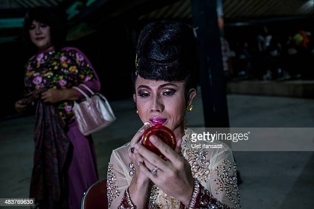 Deby a member of a Pesantren boarding school AlFatah for transgender people known as 'waria' applies makeup to her face during Syawalan tradition on...