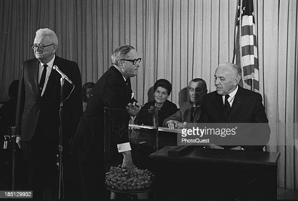 Dec 1 1969 Congressman Alexander Pirnie reaching into a container of draft numbers as others look on including retiring Selective Service Director Lt...