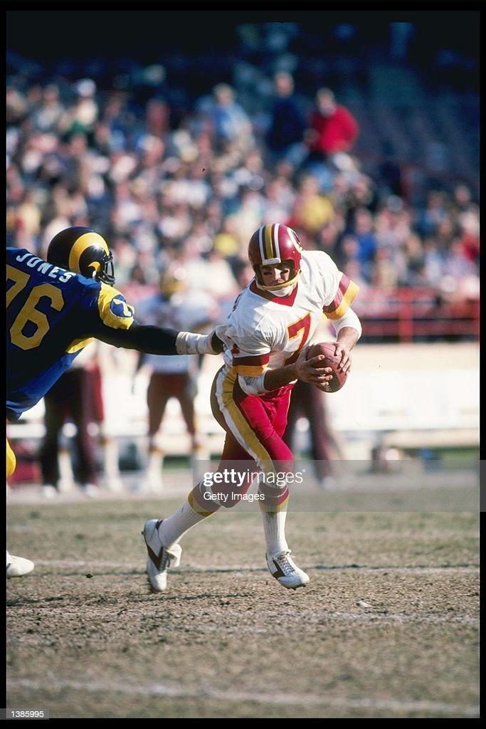 Washington Redskins quarterback Joe Theismann avoids Los Angeles Rams defensive lineman Cody Jones during game at Anaheim Stadium in Anaheim...