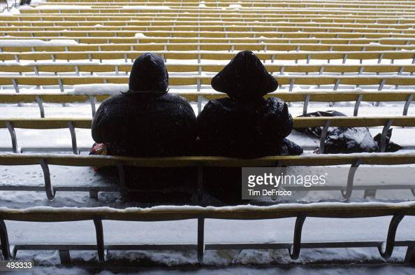 Cold Denver Bronco fans sit in snow covered benches during a game against the New York Giants at Mile High Stadium in Denver Colorado The Giants...