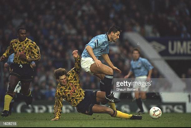 David White of Manchester City jumps over Tony Adams of Arsenal for the ball during a Divsion One match in Manchester England Mandatory Credit Shaun...