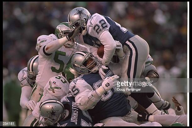 Running back Emmitt Smith of the Dallas Cowboys leaps high atop a pile of linemen and is stopped by linebacker Kurt Gouveia of the Philadelphia...