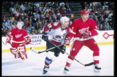Goaltender Mike Vernon of the Detroit Red wings watches as right wing Mathieu Dandenault of the Detroit Red wings and center Joe Sakic of the...