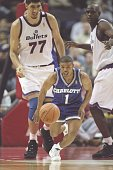 Guard Tyrone Bogues of the Charlotte Hornets dribbles the ball down the court as center Gheorghe Muresan of the Washington Bullets watches at the US...