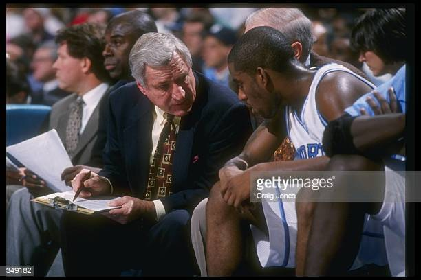 North Carolina Tar Heels head coach Dean Smith confers with guard Ed Cota during the Pepsi Challenge against the South Carolina Gamecocks at the...