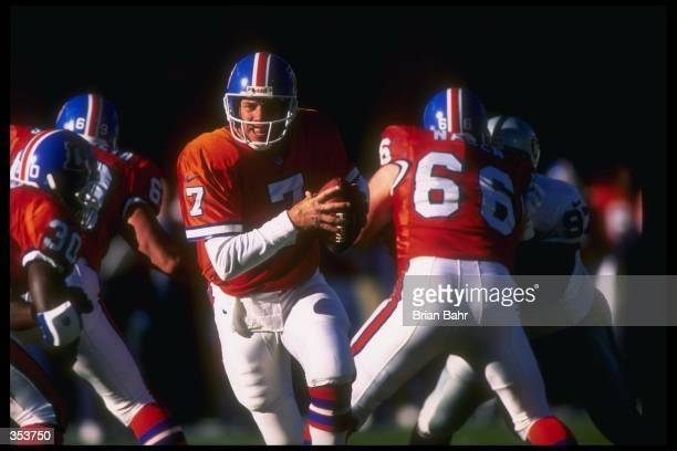 Quarterback John Elway of the Denver Broncos moves the ball during a game against the Oakland Raiders at Mile High Stadium in Denver Colorado The...