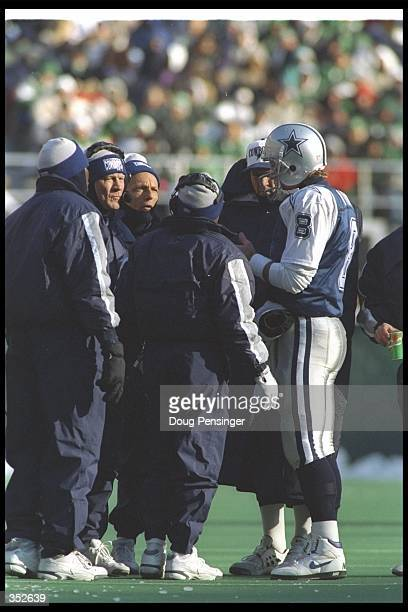 Quarterback Troy Aikman of the Dallas Cowboys confers with the coaching staff during a game against the Philadelphia Eagles at Veterans Stadium in...