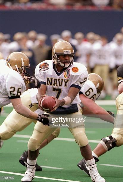 Quarterback Chris McCoy hands the ball to fullback Tim Cannada of the Navy Midshipmen during a game against the Army Cadets at the Meadowlands in...