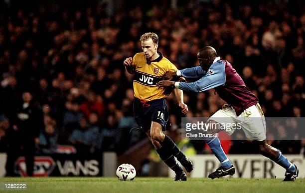 Dennis Bergkamp of Arsenal takes on Ugo Ehiogu of Aston Villa in the FA Carling Premiership match at Villa Park in Birmingham England Villa won 32...