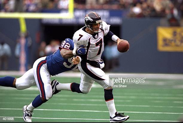 Quarterback John Elway of the Denver Broncos in action against defensive end Michael Strahan of the New York Giants during the game at Giants Stadium...