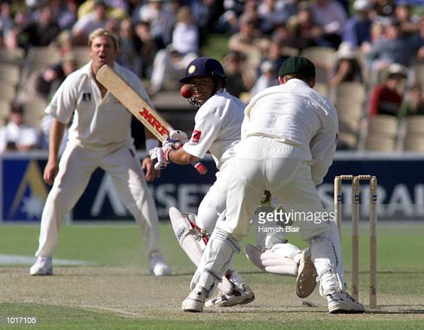 Sachin Tendulkar of India sweeps with Shane Warne and Adam Gilchrist of Australia looking on on two of the first test between Australia and India at...