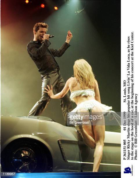 Dec 1999 St Louis MO Singer Ricky Martin sings his popular hit song Livin'' La Vida Loca as he rises to the stage on the hood of a car at the...