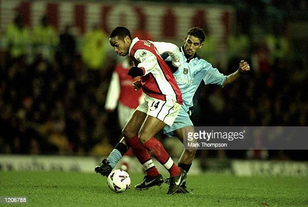 Thierry Henry of Arsenal holds the ball from Moustapha Hadji of Coventry City during the FA Carling Premier League match played at Highfield Road in...