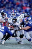 Fred Taylor of the Jacksonville Jaguars carries the ball as he is tackeld by Jeff Smith and Christian Peter of the New York Giants at the Giants...