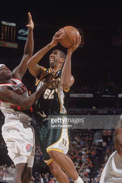 Center Calvin Booth of the Seattle SuperSonics does a layup as forward Zachary Randolph tries to block during the NBA game against the Portland Trail...