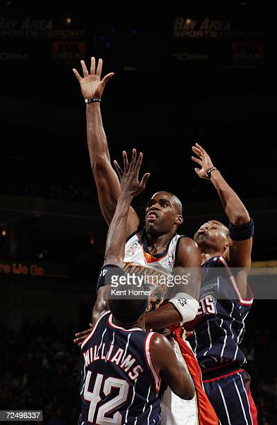 Forward Antawn Jamison of the Golden State Warriors shoots over guard Walt Williams of the Houston Rockets during the NBA game at the Arena in...