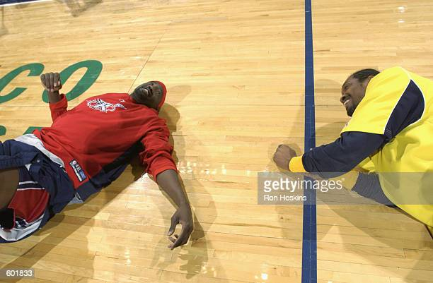 Forward Carlos Rogers of the Indiana Pacers laughs with guard Walt Williams of the Houston Rockets before the NBA game at Conseco Fieldhouse in...