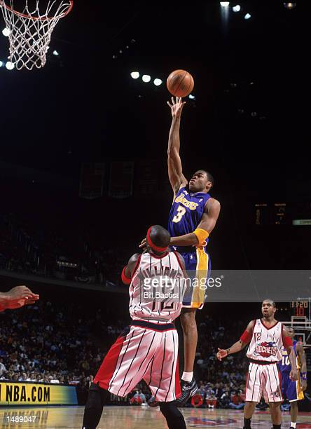 Forward Devean George of the Los Angeles Lakers shoots over guard Walt Williams of the Houston Rockets during the NBA game at the Compaq Center in...
