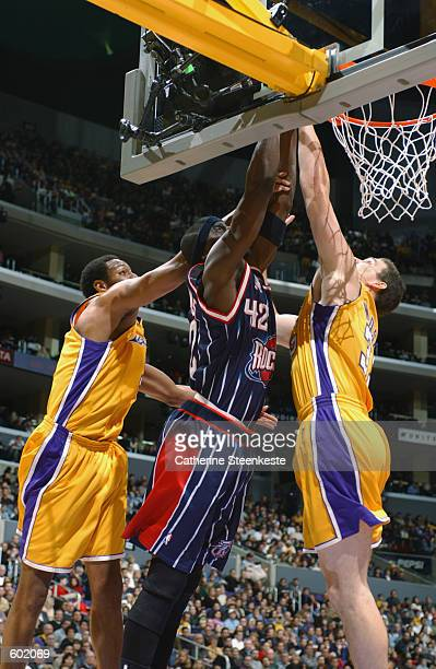 Guard Walt Williams of the Houston Rockets rebounds over forward Mark Madsen of the Los Angeles Lakers during the NBA game at Staples Center in Los...