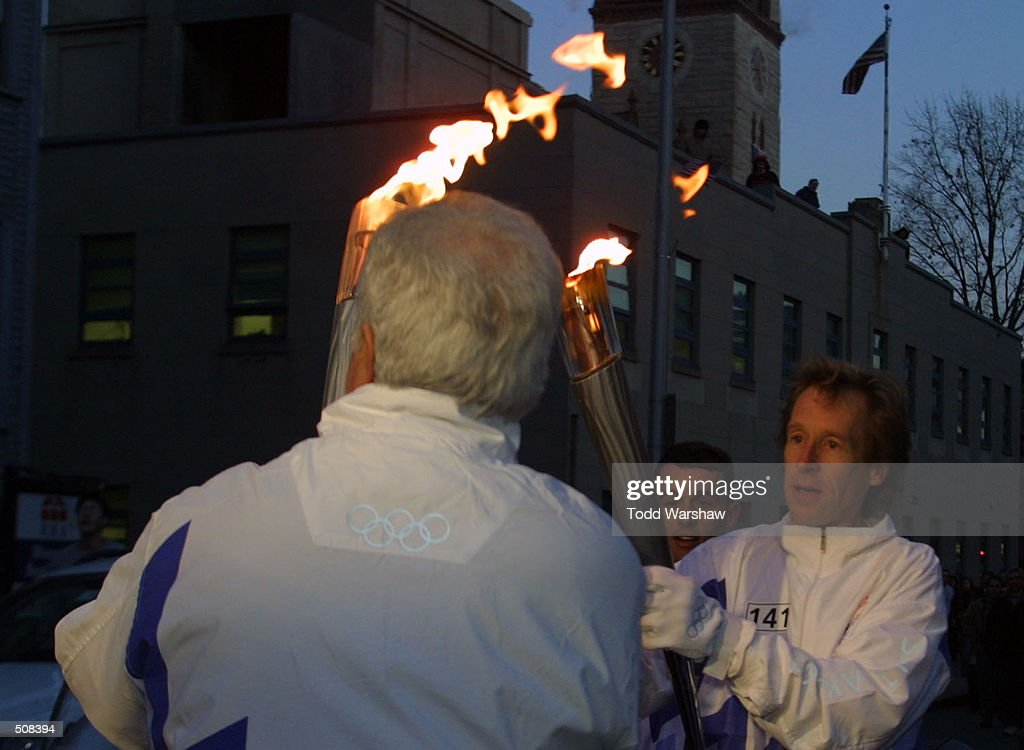 Torchbearer Bill Rodgers passes the Olympic Flame during the 2002 Salt Lake Olympic Torch Relay in Cambridge Massachussetts DIGITAL IMAGE Mandatory...