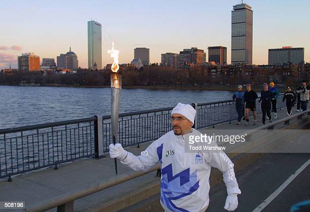 Torchbearer Geoffrey Hennessy carries the Olympic Flame during the 2002 Salt Lake Olympic Torch Relay in Cambridge Massachussetts DIGITAL IMAGE...