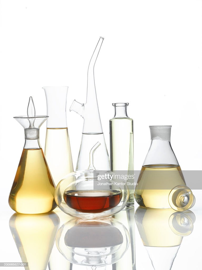 Decanter filled with different oil against white background
