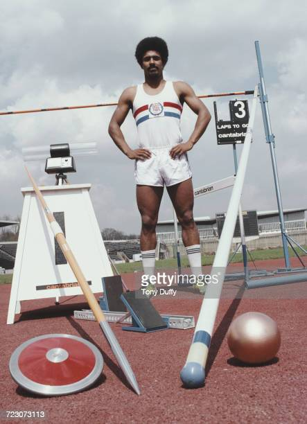 Decathlete Daley Thompson of Great Britain poses for a portrait on the long jump track with a pole vault javelin discus shot put hurdles high jump...