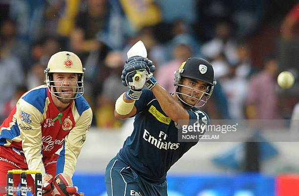 Deccan Chargers batsman Jean Paul Duminy is watched by Royal Challengers Bangalore wicketkeeper AB de Villiers as he plays a shot during the IPL...