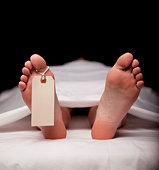 DSLR photo of deceased person laying on back, on table, covered in white sheet with toe tag attached. Selective focus fades to black background.