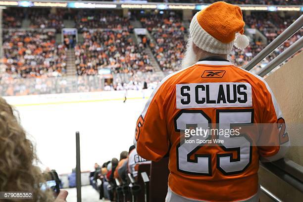 Fan dressed as Santa Claus wears a Flyers uniform and hat while watching the game from the stands during an NHL game between the Canadiens and the...