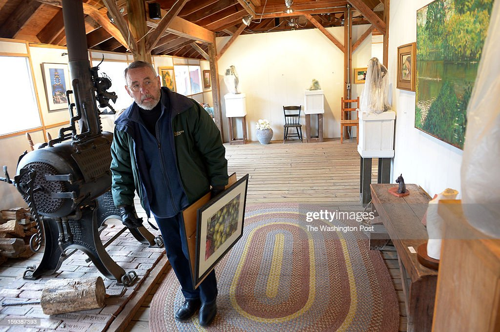 Tony Mendez (the CIA agent from Argo) carries a few of his wife's photographs that were recently sold into the house from their home art gallery on December 12, 2012 in Knoxville, MD