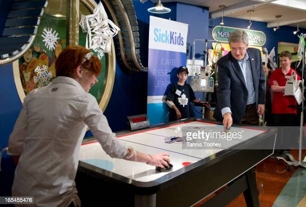 December 18 2010PM Stephen Harper plays a quick game of air hockey with Kaitlyn O'Brien from Stouffville Ontario They are playing on the table he...