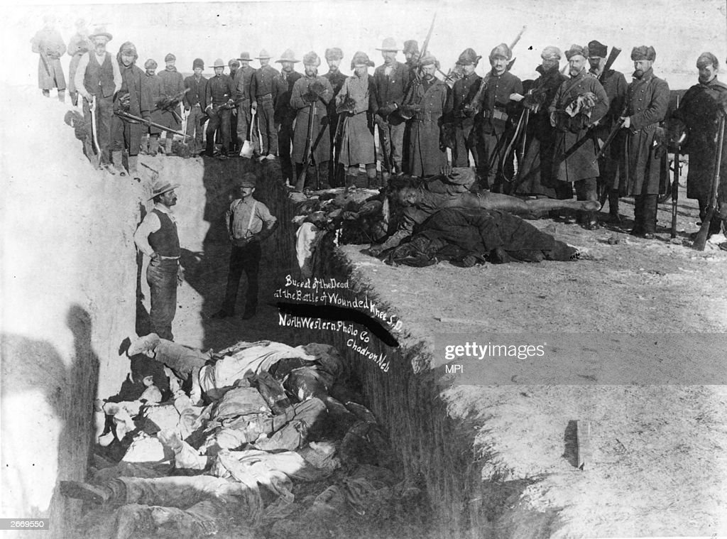 Bodies of Sioux Indians being unceremoniously piled into a mass grave hacked into the frozen Dakota soil after the tragedy at Wounded Knee South...