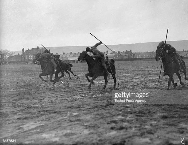 Canadian rough riders lance tentpegging during training