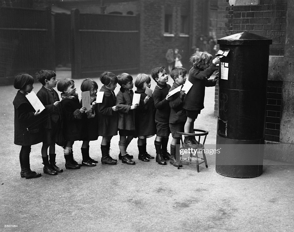 Schoolchildren posting letters in the playground of the Red Lion Street School.
