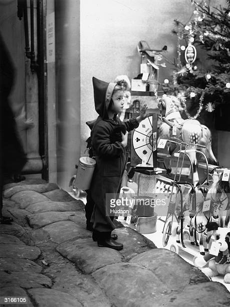 A seasonably attired young shopper climbs on to the sandbags to get a closer look at the toys in a shop window in the West End of London