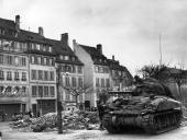 A French gendarme and a citizen of Strasbourg chat to an American soldier in a tank The street is littered with piles of rubble
