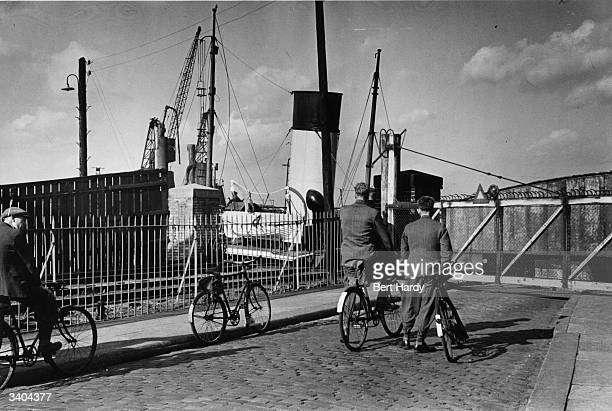People on bicycles wait for a bridge gate to open near the West India Dock in East London Original Publication Picture Post 4931 The Pool Of London...