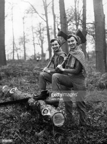 Twins Pamela and Pauline Chamberlain having a rest from cutting up yule logs in woods near Bracknell in Berkshire