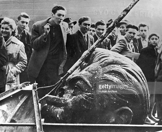 A crowd of people surround the demolished head of a statue of Josef Stalin including Daniel Sego the man who cut off the head during the Hungarian...