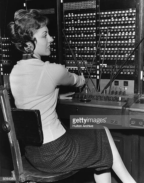 A telephonist operating a switchboard at the exhibition of historical telephone apparatus at Fleet Building Farringdon Street London