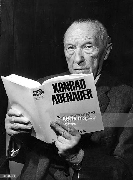 German statesman and three times chancellor Konrad Adenauer holding his recently published memoirs shortly before his 90th birthday