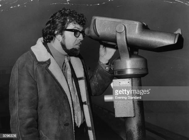 Popular Australian entertainer and recording artiste Rolf Harris surveys the runways at London Airport through a telescope