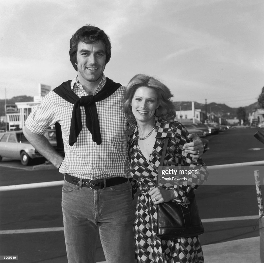 American actor Tom Selleck poses outdoors with his first wife, actor Jacquelyn Ray, Los Angeles, California. Selleck was a regular on the daytime television dramatic series, 'The Young and the Restless.' He wears a sweater tied around his neck.