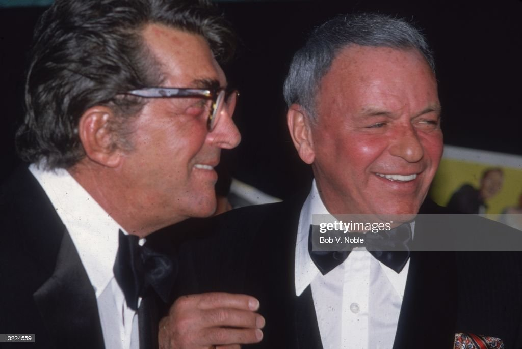 American actors and singers Frank Sinatra and Dean Martin (1917 - 1995) (L) smiling and looking off camera at Caesar's Palace, Las Vegas, Nevada. Sinatra had received the Pied Piper Award from ASCAP (American Society of Composers, Authors and Publishers) celebrating both his 40th year in show business and his 64th birthday.